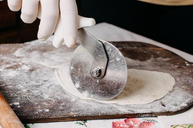 Vlees qutab tijdens het maken van deeg koken op bruin hout rustiek bureau