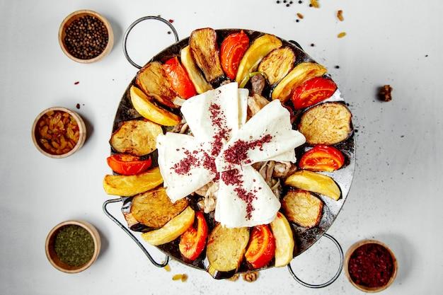 Vlees salie met aardappelen aubergine en pitabroodje bovenaanzicht