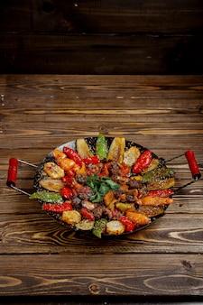 Vlees salie met aardappelen paprika en aubergine gekookt op houtskool
