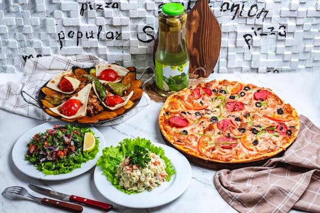 Vlees salie met salami pizza hoofdsalade groente salade en compote op tafel