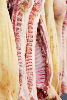 Vlees snijden en verwerken. varkenskarkassen tegen het oppervlak van een vleesverpakkingsinstallatie. slachthuis.