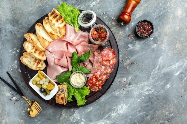 Vlees voorgerecht, antipasto schotel koud vlees bord met prosciutto, plakjes ham, salami, versierd met basilicum, tomaten en olijvensalade. banner, menu, receptplaats voor tekst, bovenaanzicht