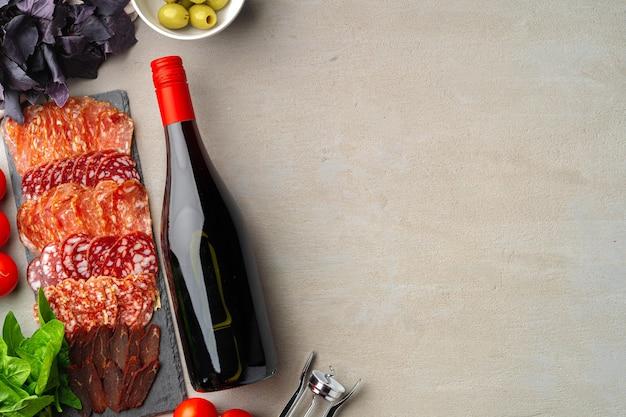 Vlees worst snijden en wijn op grijze achtergrond