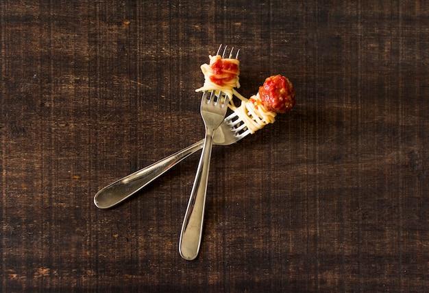 Vleesballen en trenette op vorken over de houten achtergrond