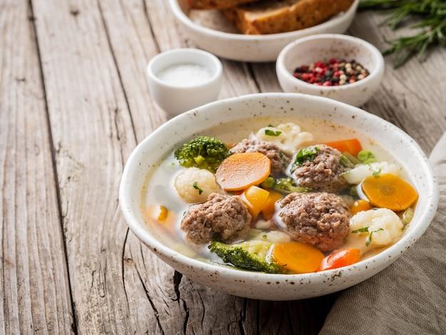 Vleesballetjes soep in witte plaat op oude houten rustieke grijze tafel, zijaanzicht