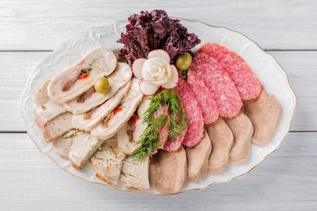 Vleesbord met heerlijke stukjes gesneden ham, worst, olijven, rundvleestong, kruiden en vlees met radijs op wit bord en houten tafel