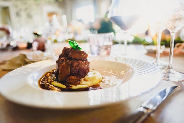 Vleesgerecht elegant geserveerd in een luxe bruiloft in een evenementenrestaurant.