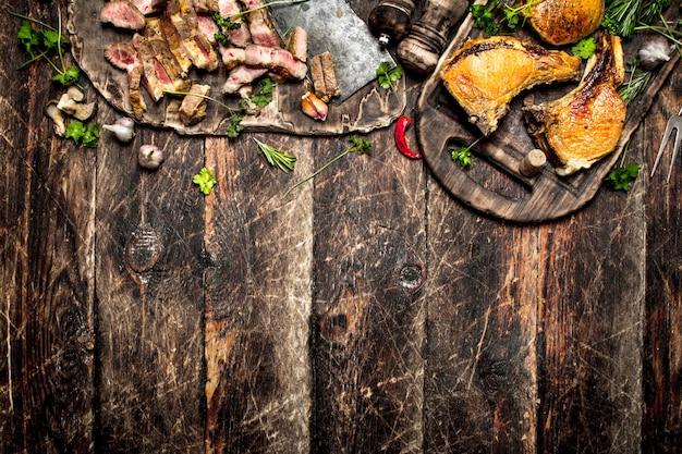 Vleesgrill. biefstuk van varkensvlees gegrild met kruiden en champignons op het bord. op de oude houten tafel.
