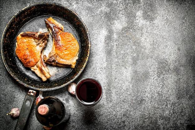 Vleesgrill. gebakken varkensvlees in de pan met rode wijn op rustieke tafel.
