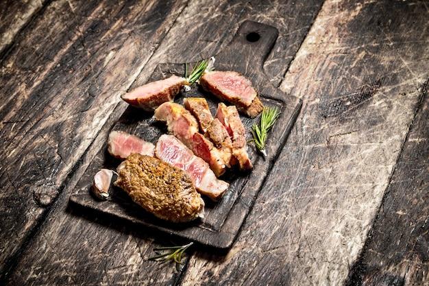 Vleesgrill. gegrilde biefstuk varkensvlees met kruiden en specerijen. op de oude houten tafel.