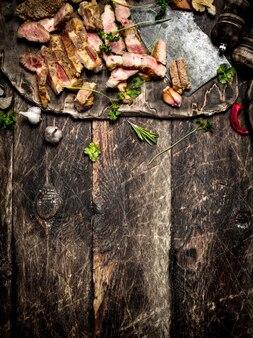Vleesgrill. gesneden gegrild varkensvlees met een oude bijl, specerijen en kruiden. op de oude houten tafel.
