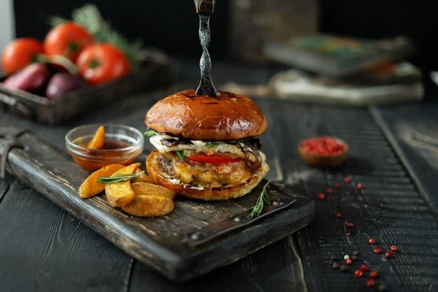 Vleeshamburger met plakken van aardappelen in de schil en tomatensaus op uitstekende houten raad