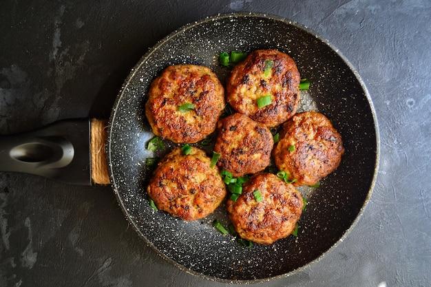 Vleeskoteletten. koteletten in een pan op een zwarte betonnen tafel .. heerlijk lekker eten. bovenaanzicht