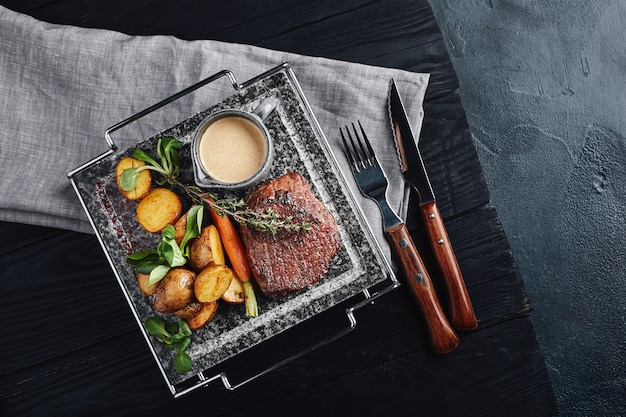 Vleeslapje vlees met gebakken krieltjes en groenten op een marmeren plaat.