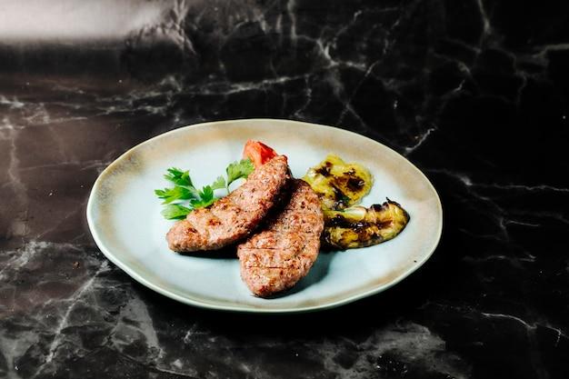 Vleeslapje vlees met geroosterde aubergines, peterselie en tomaat in witte plaat.