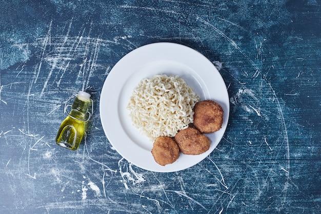 Vleesnuggets met noedels en olijfolie.