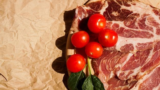 Vleesplakken en kersentomaten. ingrediënten voor sandwich en bruschetta. snacks koken. spinazie bladeren.