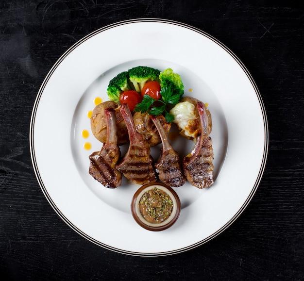 Vleesribben in een saus met aardappelen in de schil en broccoli