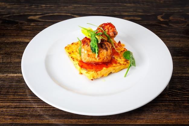 Vleesrolletjes op een omelet met spinazie en karamelsaus op een witte plaat.