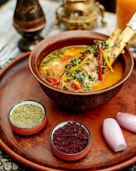 Vleessoep met groenten geserveerd met uien berberis en kruiden