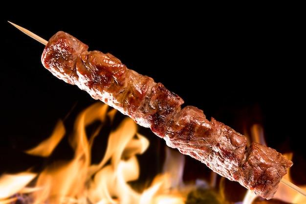Vleesspies boven vuurvlammen