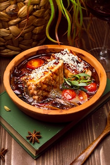 Vleesstoofpot met groenten, tomaten. goelasjsoep op een boek