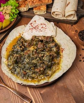 Vleesstoofpot, turshu, sebze govurma met uien, groene kruiden, wortels in bouillon saus