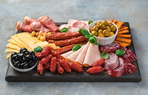 Vleesvoorgerecht, assortiment van worst, kaas, olijven en basilicum op een grijze achtergrond.