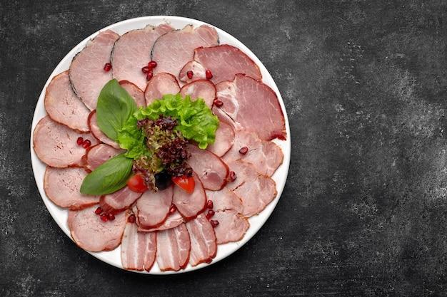 Vleeswaren dun gesneden, worst, spek, gekookt varkensvlees, vlees, met sla, basilicum, cherrytomaatjes en granaatappelpitjes, op een witte plaat