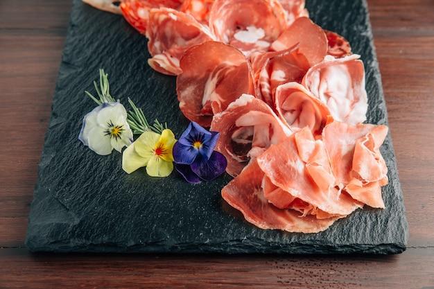 Vleeswaren op stenen plaat met prosciutto, spek, salami en worstjes.