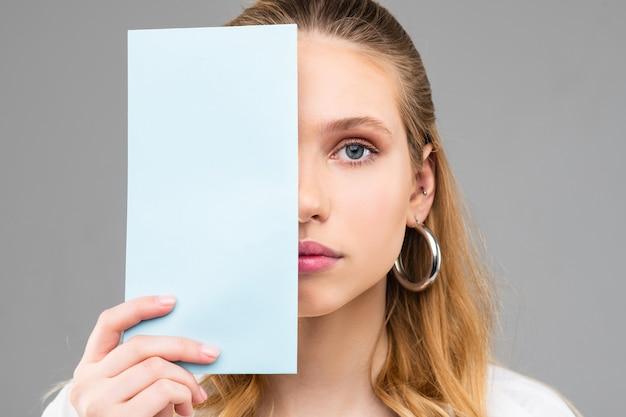 Vlekkeloze volwassen vrouw met dikke oorbellen en licht haar dat een deel van haar gezicht sluit met een lichtblauw bord