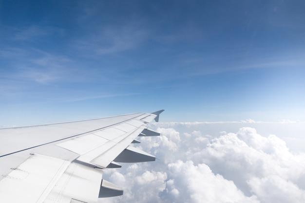 Vleugel van een vliegtuig dat boven de ochtendwolken vliegt