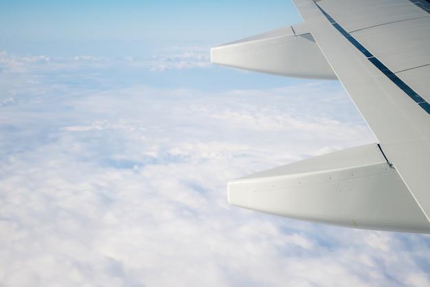 Vleugel van een vliegtuig dat boven de ochtendwolken vliegt.