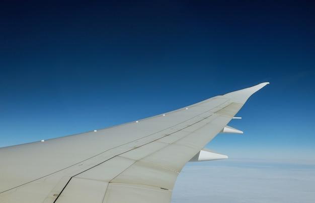 Vleugel van een vliegtuig dat boven de wolken van een vliegtuig vliegt