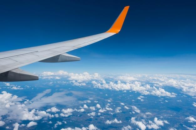 Vleugel van een vliegtuig dat boven de wolken vliegt