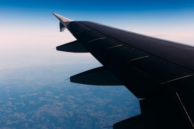 Vleugel van het vliegtuig boven de blauwe hemel