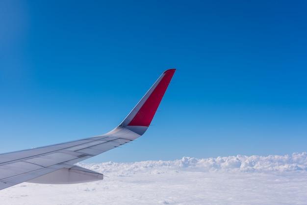 Vleugel van het vliegtuig met blauwe lucht en wolken