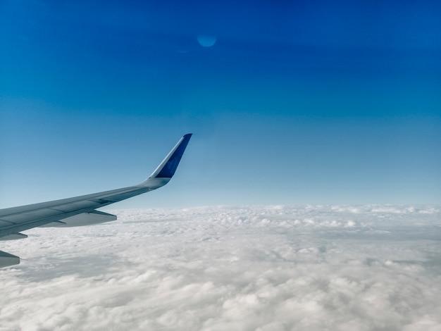 Vleugel van het vliegtuig op witte wolken