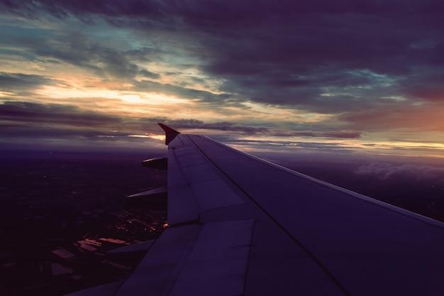 Vleugel van vliegtuig die boven de donkere regenwolken vliegen bij zonsondergang in bangkok