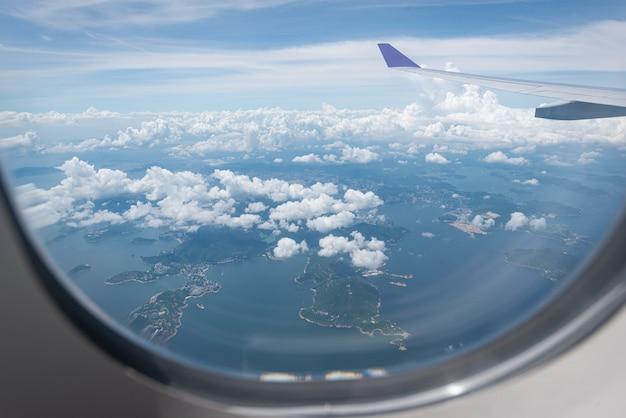 Vleugel van vliegtuig die boven hong kong-stadsachtergrond door het venster vliegen.