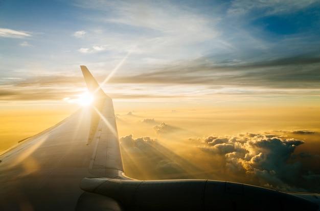 Vleugel van vliegtuig op blauwe hemel in schemering en zonsondergang