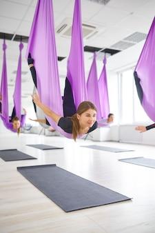 Vlieg anti-zwaartekracht yoga, groepstraining met hangmatten. een mix van fitness, pilates en dansoefeningen. vrouwen op yogi-training in sportstudio