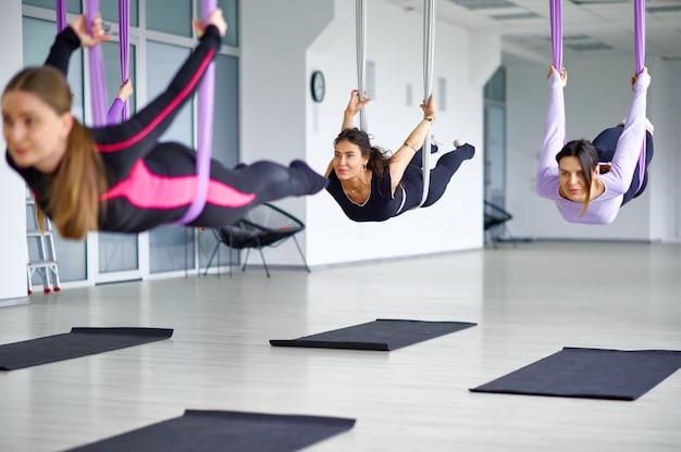 Vlieg anti-zwaartekracht yoga, vrouwelijke groepstraining met hangmatten. een mix van fitness, pilates en dansoefeningen. vrouwen op yogatraining in sportstudio