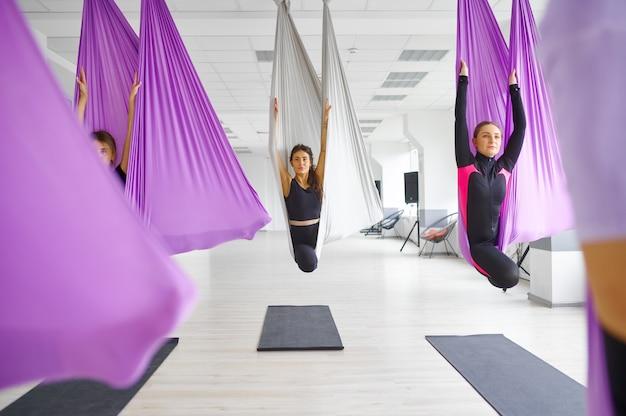 Vlieg yoga, vrouwelijke groepstraining, hangmatten. een mix van fitness, pilates en dansoefeningen. vrouwen op yogi-training in sportstudio