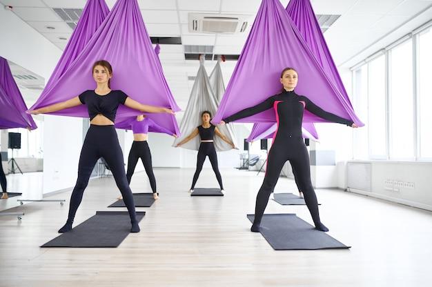 Vlieg yoga, vrouwelijke groepstraining met hangmatten. een mix van fitness, pilates en dansoefeningen. vrouwen op yogi-training in sportstudio