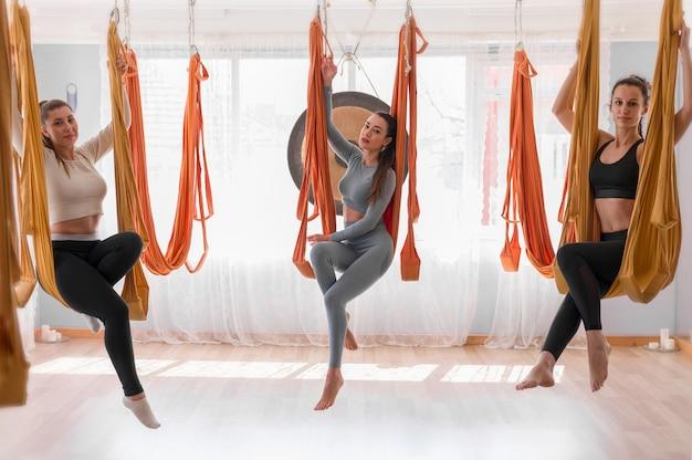 Vlieg yogagroep vrouwen in hangmatten
