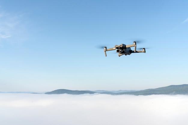 Vliegen met een quadrocopter-helikopterdrone in de lucht in een heldere blauwe lucht ochtendmist en bergen belo...