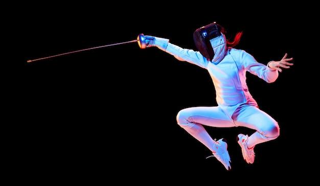 Vliegen. tienermeisje in hekwerkkostuum met in hand zwaard geïsoleerd op zwarte muur, neonlicht. jong model oefenen en trainen in beweging, actie. copyspace. sport, gezonde levensstijl. folder.