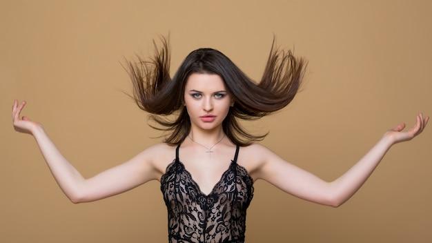 Vliegend golvend haar. mooie brunette meisje in sexy zwarte veters combo jumpsuit. mode lingerie. luxe vrouw.