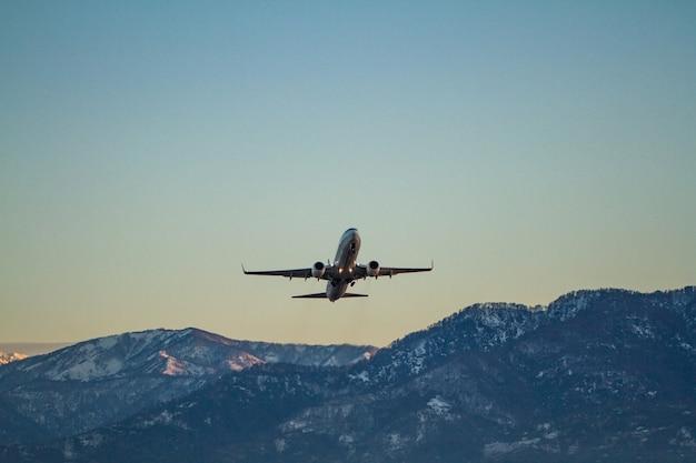 Vliegend vliegtuig op een surfce van blauwe lucht en bergen